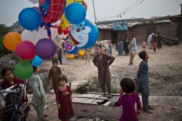 Pakistani and Afghan refugee children gather by a balloon vendor on the outskirts of Islamabad, Pakistan, Tuesday, Aug. 5, 2014.(AP Photo/Muhammed Muheisen)