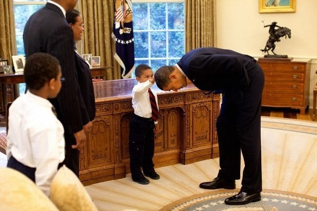 may-8-2009-president-barack-obama-bends-over-so-the-son-of-a-white-house-staff-member-can-pat-his-head-during-a-visit-to-the-oval-office-in-washington-dc-620x413