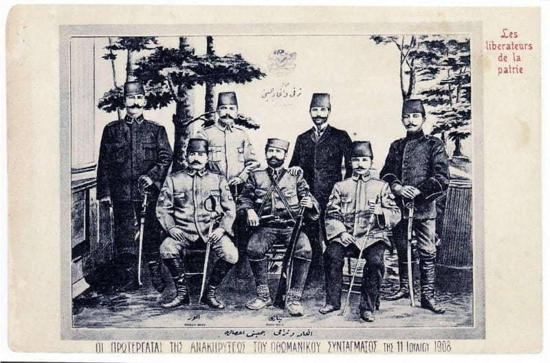 """Oturanlar soldan sağa Eyüp Sabri, Resneli Niyazi ve Enver Bey. Sağ üst köşede Fransızca: """"Vatanın Kurtarıcıları"""""""